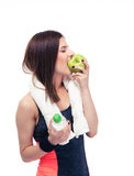 Sportieve vrouw die appel eten en fles met water houden Stock Foto