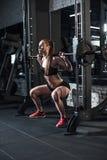 Sportieve vrouw die barbell bij gymnastiek opheffen Stock Afbeeldingen