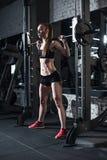 Sportieve vrouw die barbell bij gymnastiek opheffen Royalty-vrije Stock Fotografie