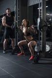 Sportieve vrouw die barbell met trainer dichtbij langs bij gymnastiek opheffen Royalty-vrije Stock Foto's