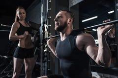 Sportieve vrouw die barbell met trainer dichtbij langs bij gymnastiek opheffen Royalty-vrije Stock Afbeelding