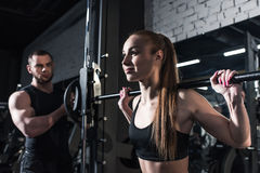 Sportieve vrouw die barbell met trainer dichtbij langs bij gymnastiek opheffen Stock Foto's