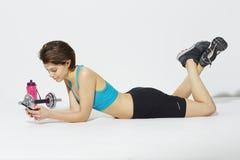Sportieve vrouw die celtelefoon met behulp van Royalty-vrije Stock Fotografie