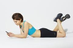 Sportieve vrouw die celtelefoon met behulp van Royalty-vrije Stock Foto