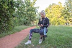 Sportieve vrouw die een onderbreking nemen en aan muziek luisteren royalty-vrije stock fotografie