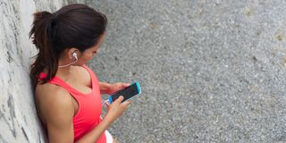 Sportieve vrouw die een rust voor het texting op smartphone nemen stock foto's