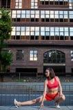 Sportieve vrouw die en benen uitrekken opwarmen alvorens stedelijke geschiktheidstraining in werking te stellen Sport en gezond l stock afbeelding
