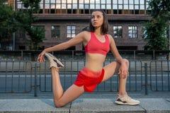 Sportieve vrouw die en benen uitrekken opwarmen alvorens stedelijke geschiktheidstraining in werking te stellen Sport en gezond l stock foto