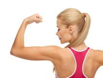 Sportieve vrouw die haar bicepsen tonen royalty-vrije stock afbeeldingen