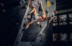 Sportieve vrouw die kunstmatige kei binnen beklimmen royalty-vrije stock foto