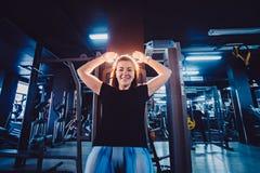 Sportieve vrouw die machine voor benen met behulp van bij de gymnastiek Mooi brunette die in een simulator uitoefenen stock foto