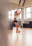 Sportieve vrouw die met gymnastiek- ringen uitoefenen Stock Fotografie
