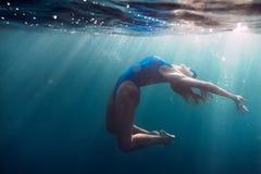Sportieve vrouw die in overzees, onderwater in blauwe oceaan drijven Royalty-vrije Stock Afbeeldingen