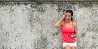 Sportieve vrouw die smartphone gebruiken stock foto