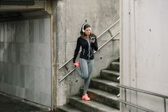Sportieve vrouw die smartphone voor het luisteren muziek gebruiken terwijl zich het uitrekken stock afbeeldingen