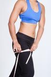 Sportieve vrouw met het meten van band rond heup. stock foto's