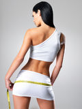 Sportieve vrouw met slank lichaam dat heupen meet royalty-vrije stock afbeelding