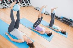 Sportieve vrouwen die ballen tussen enkels in geschiktheidsstudio houden stock afbeelding