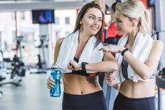 sportieve vrouwen die met handdoeken fitnes resultaten met slim horloge na opleiding controleren stock fotografie