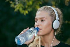 Sportieve vrouwen tdrinking water en het luisteren aan muziek stock afbeelding
