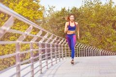Sportieve vrouwenjogging en het uitoefenen in het park Stock Afbeeldingen