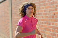 Sportieve vrouwenjogging op middelbare leeftijd door stad royalty-vrije stock afbeeldingen