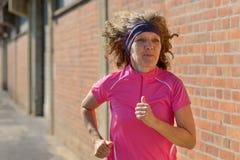 Sportieve vrouwenjogging op middelbare leeftijd door stad stock afbeeldingen