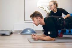 Sportif établissant sur le plancher avec l'entraîneur personnel photos libres de droits