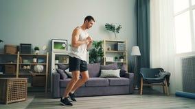 Sportif beau dans l'habillement élégant faisant des exercices physiques à la maison clips vidéos