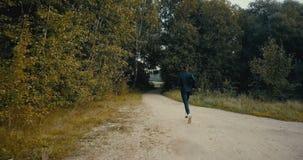 Sportif courant à une ouverture de chemin forestier Vue arrière de bourdon Athlète déterminé motivé sur le chemin de pays croisé  clips vidéos