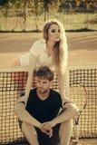 Sportif d'étreinte de fille s'asseyant au filet de tennis sur la cour d'argile Images stock