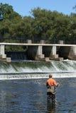 Sportif dans les échassiers pêchant au barrage Photo libre de droits