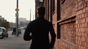 Sportif en temps réel courant rapidement dans une vieille rue Les jeunes libèrent l'entraîneur masculin professionnel déterminé d clips vidéos