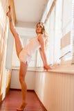 On sportif, jeune femme élégante de belle fille blonde flexible a soulevé la jambe dans la fente parallèle au mur dans des pyjama Photographie stock