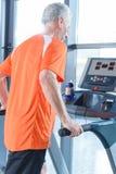 Sportif mûr s'exerçant sur le tapis roulant dans le gymnase Photo libre de droits