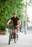 Sportif masculin posant sur le vélo près des arbres verts Image libre de droits