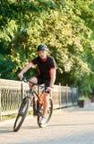 Sportif masculin posant sur le vélo près des arbres verts Photographie stock libre de droits