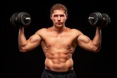 Sportif musculaire sans chemise avec le visage sérieux et haltères dans des ses mains Photographie stock libre de droits