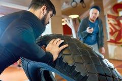 Sportif renversant le pneu dans le gymnase photo libre de droits