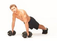 Sportif sans chemise musculaire faisant des pousées avec des haltères sur le fond blanc Photographie stock libre de droits