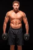 Sportif sans chemise musculaire sérieux se tenant avec des haltères sur le fond noir Photographie stock