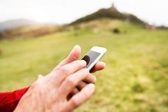 Sportif supérieur méconnaissable en nature avec le téléphone intelligent Photo libre de droits