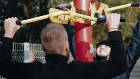 Sportifs faisant des exercices sur des simulateurs dehors banque de vidéos