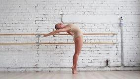 Sportig blond caucasian kvinna i den beigea bodyen som gör praktiserande balettförehavanden arkivfilmer