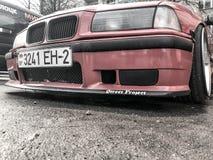 Sportig BMW röd bil med härliga stora tävlings- hjul med mycket låg jordrensning på den skinande ensemblen Vitryssland Minsk, mar royaltyfria bilder