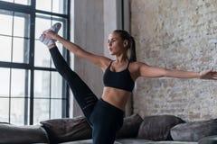 Sportig Caucasian flicka som gör stående kluven övning i hennes lägenhet med vindinre royaltyfri bild