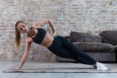 Sportig Caucasian flicka som inomhus gör abs för övning för sidoplankastjärna funktionsduglig och sneda muskler mot tegelstenvägg arkivbilder