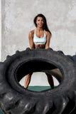 Sportig flickaövning med det stora gummihjulet Arkivbild