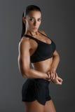 Sportig flicka med muskler royaltyfri foto