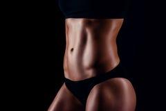 Sportig flicka med stora muskler i svart sportswear Brunbränd ung idrotts- kvinna En kvinnlig kropp för stor sport royaltyfria foton